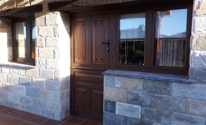 Aluminios Tecnoal - puerta en dos secciones, con ventana incluida de acceso a vivienda particular en aluminio imitación a madera y estilo rústico