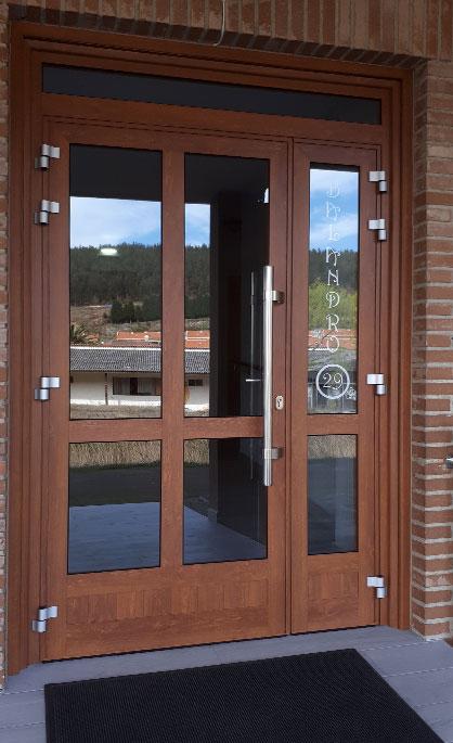Aluminios Tecnoal - puerta en dos secciones, con fijo incluido de acceso a edificio en aluminio imitación a madera y estilo moderno