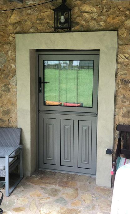 Aluminios Tecnoal - puerta en dos secciones, con ventana incluida de acceso a vivienda particular en aluminio color gris y estilo rústico