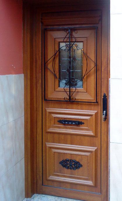 Aluminios Tecnoal - puerta de acceso a vivienda particular en aluminio imitación a madera y estilo rústico y enrrejado