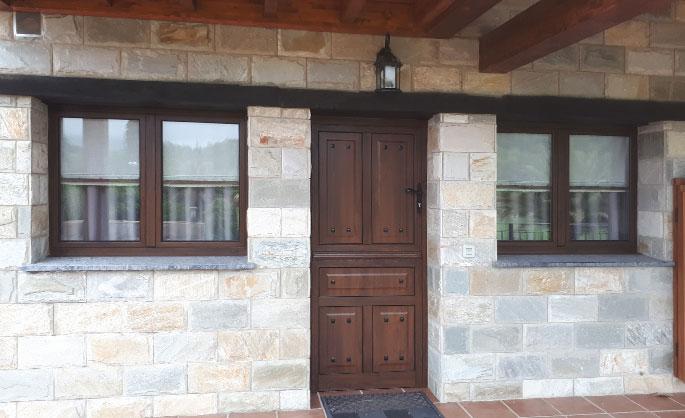 Aluminios Tecnoal - puerta de acceso a vivienda particular en aluminio imitación a madera y estilo rústico